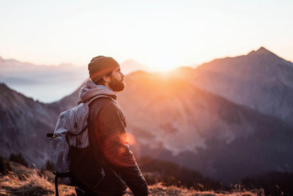 Backpacker auf Berg stehend und Sonnenuntergang