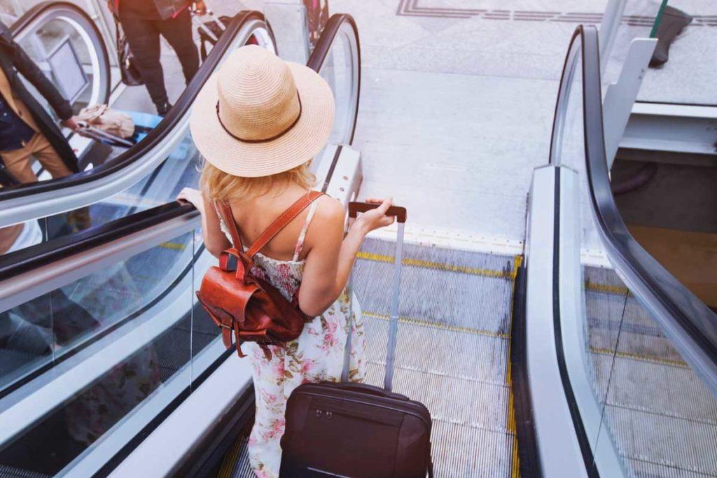 Reisende am Flughafen mit Koffer