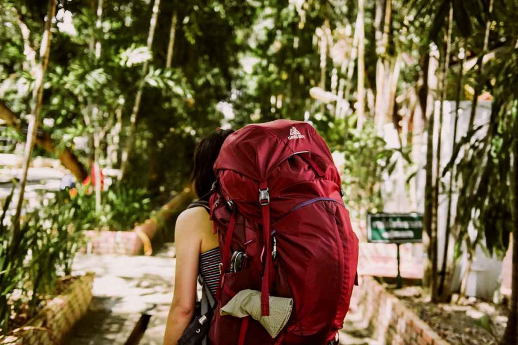 Woman with packed backpack on a budget travel trip