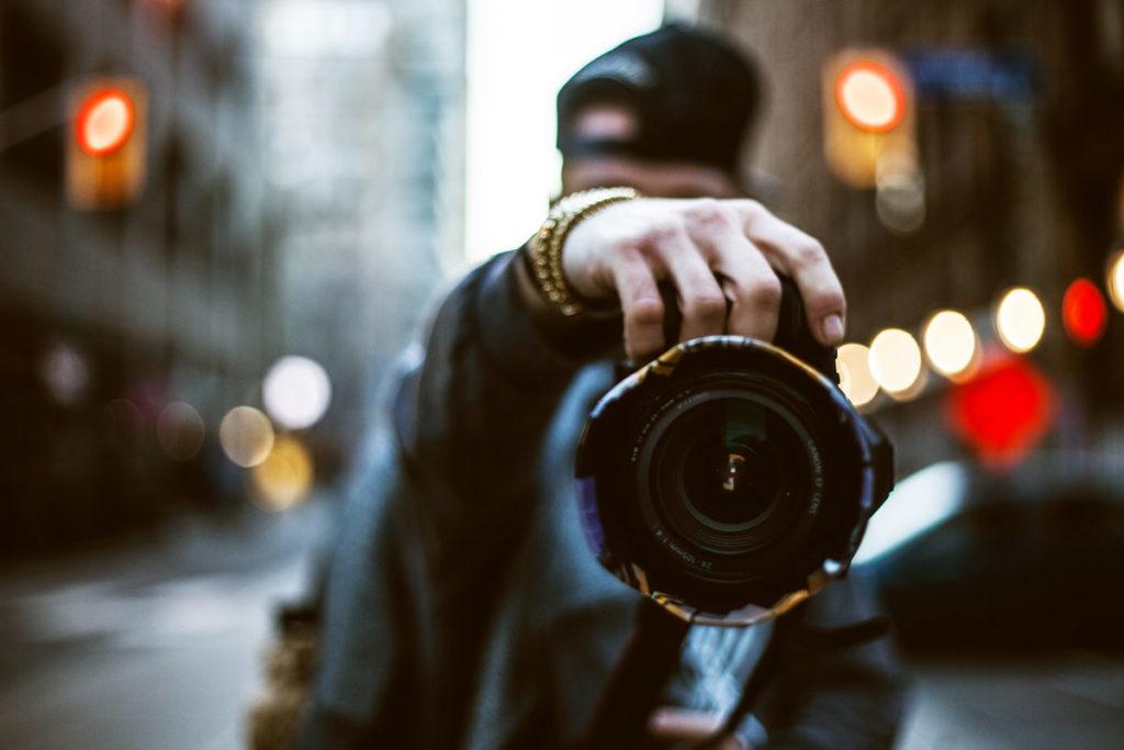 Person frontal stehend mit Kamera in der Hand in der Stadt