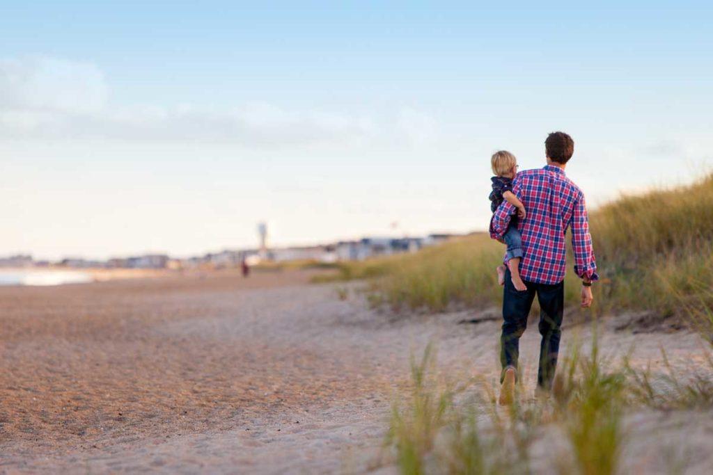 Vater und Kind spazierend am Strand