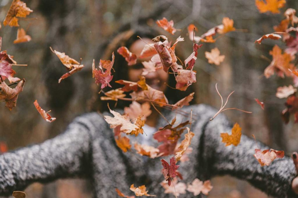 Woman throwing leaves in the air in the forest