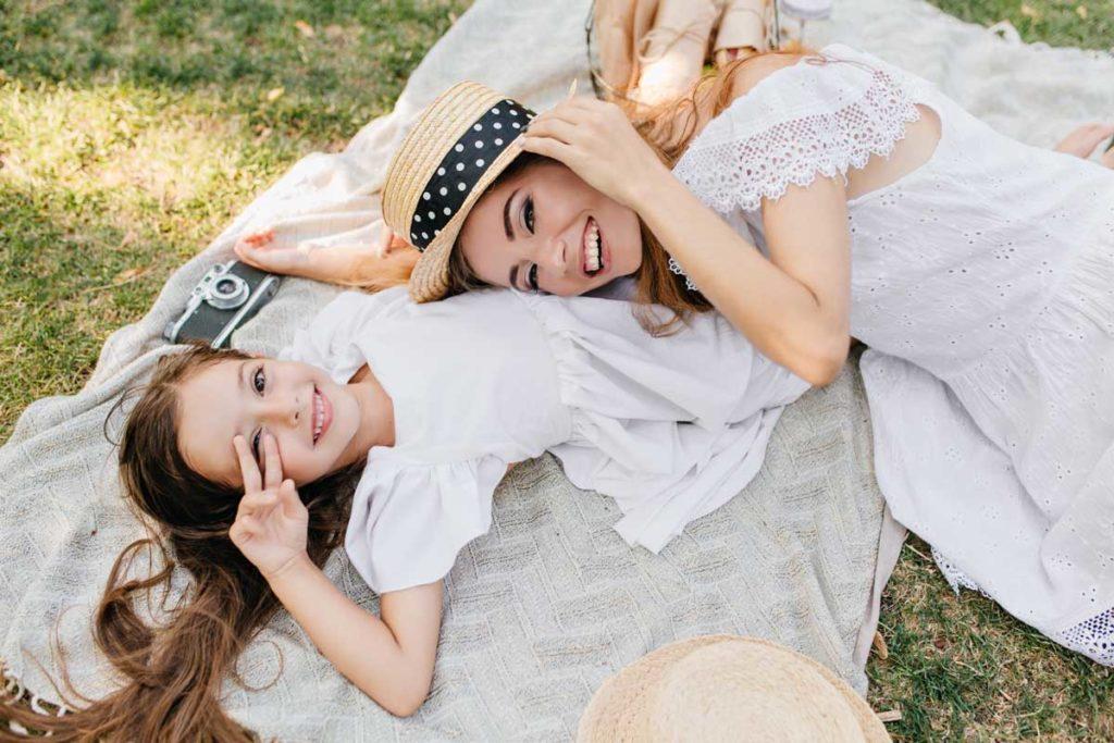 Mutter und Tochter für perfektes Familienfoto liegend im Gras