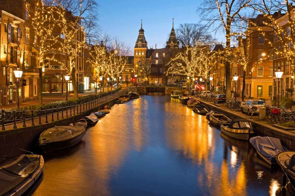 Weihnachtlich beleuchteter Kanal mit Booten in Amsterdam, Niederlande