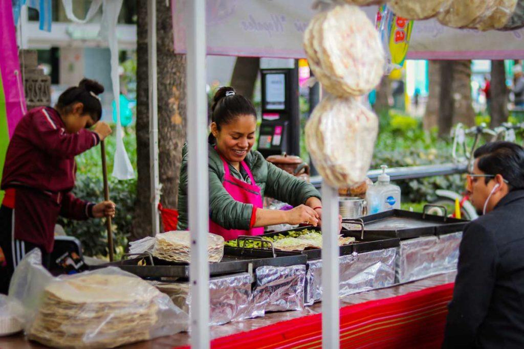 Frau bereitet traditionelles mexikanisches Essen auf Straßenmarkt zu