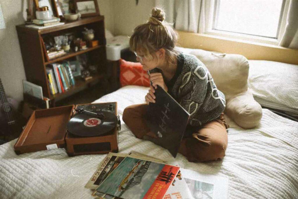 Eine Frau sitzt auf dem Bett und hört Musik zu