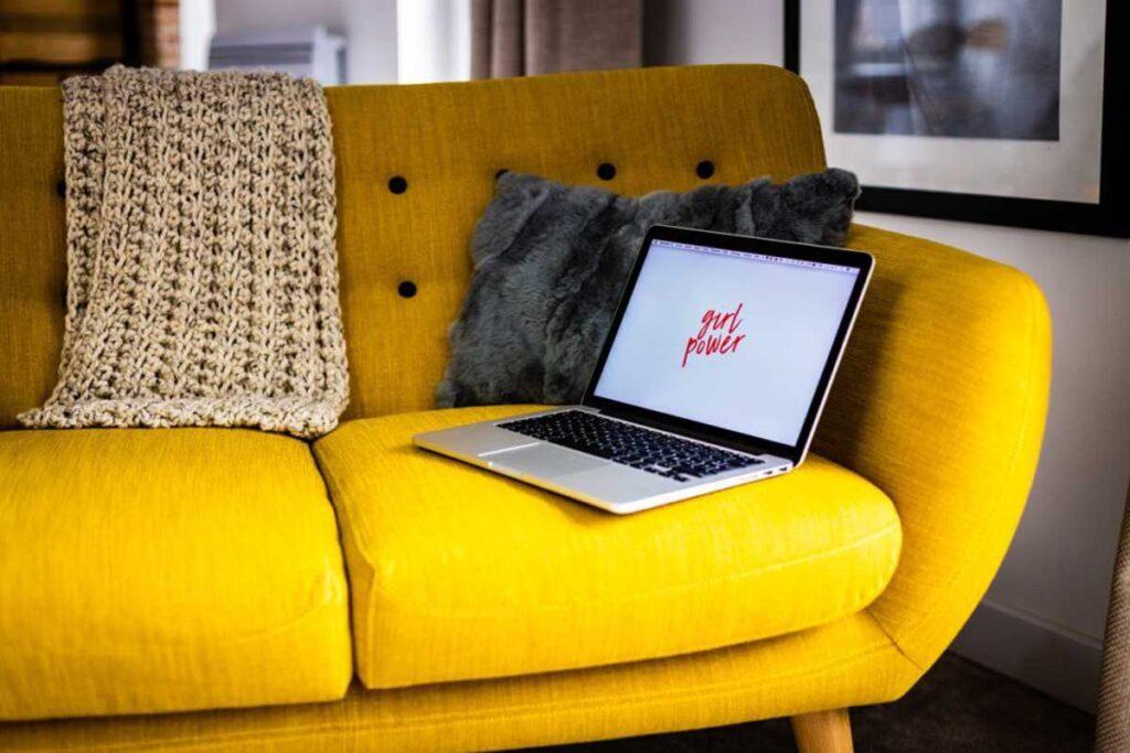 Ein Computer sitz auf eine gelben Couch