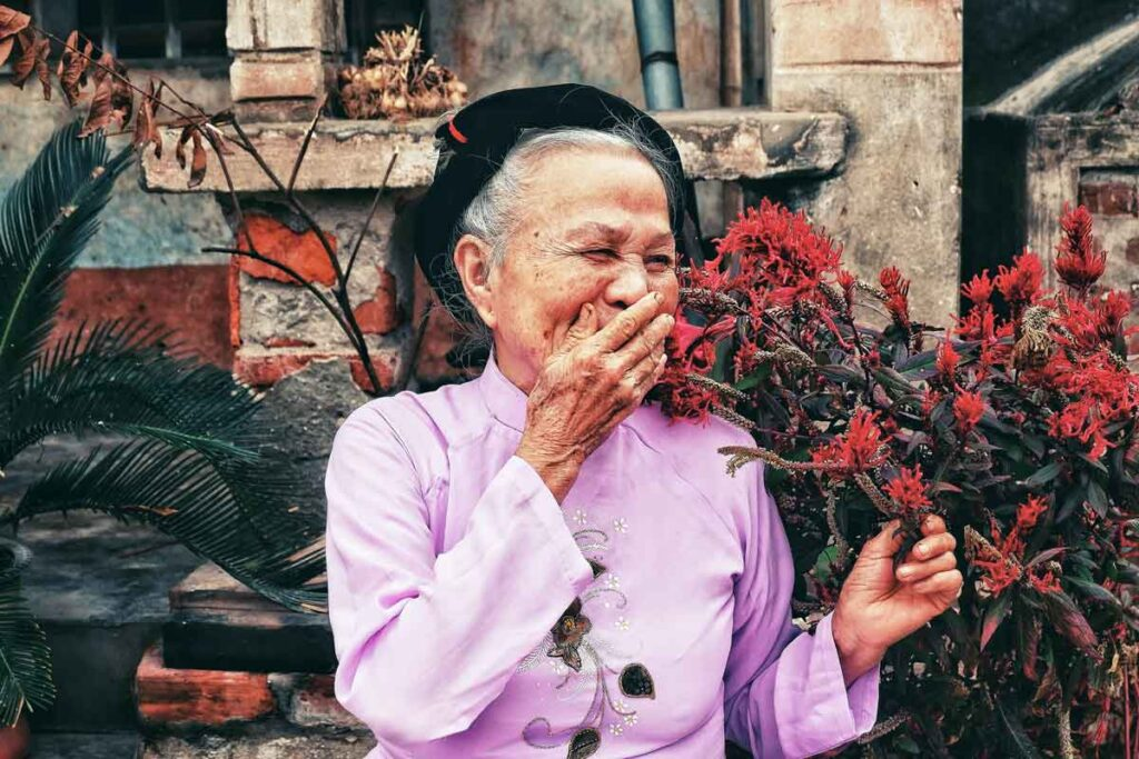 An elderly woman laughs in front of red flowers