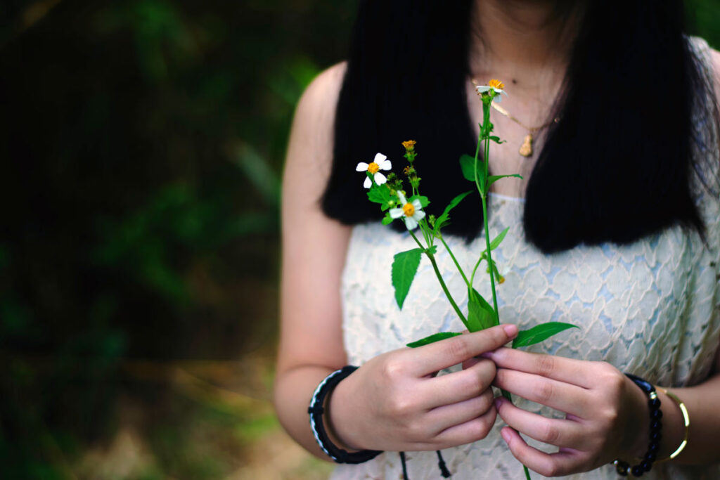 Woman holding a flowering plant for Mother's Day 2020
