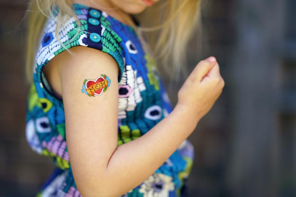 Ein kleines Mädchen hat ein 'Mom' Abzieh Tattoo für Muttertag 2020