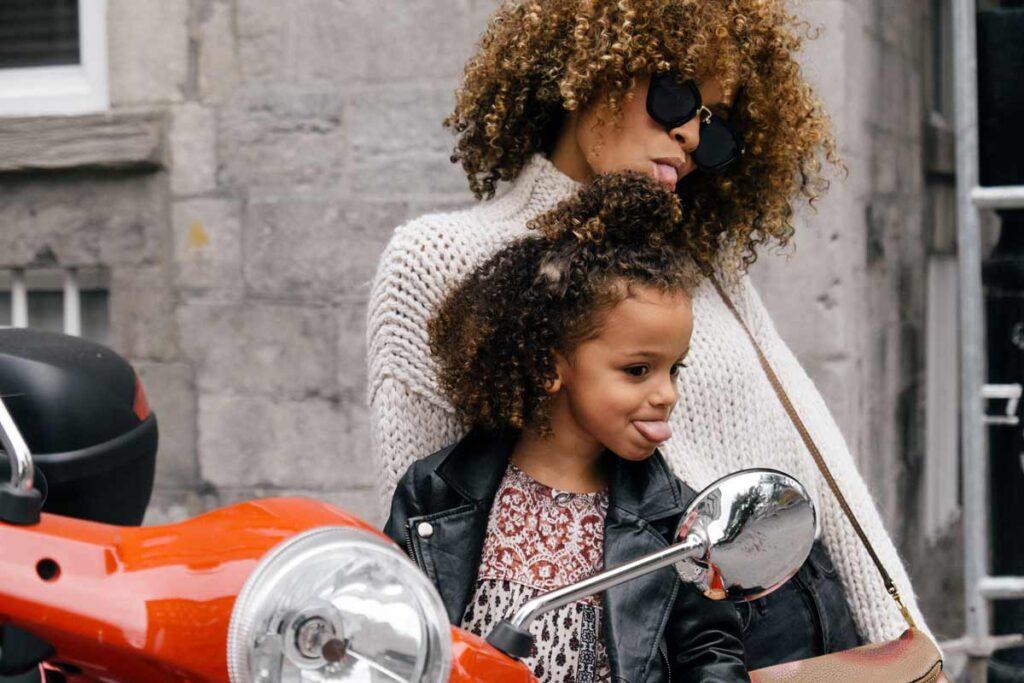 Eine Mutter und Tochter posieren zusammen neben ein Motorrad.
