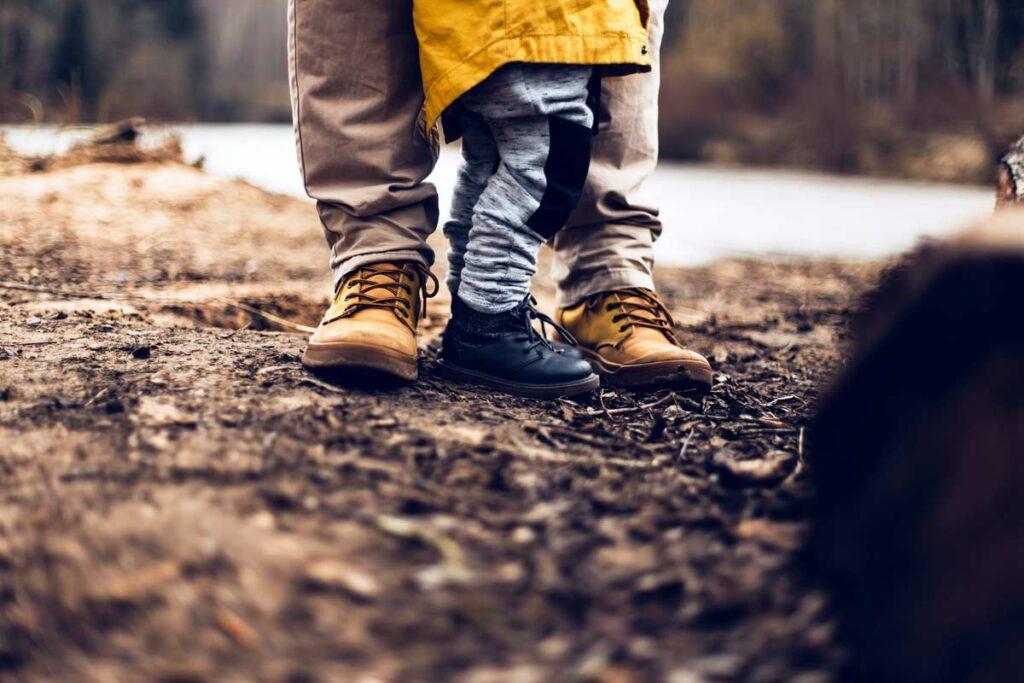 Ein Kind steht draußen neben sein Elternteil