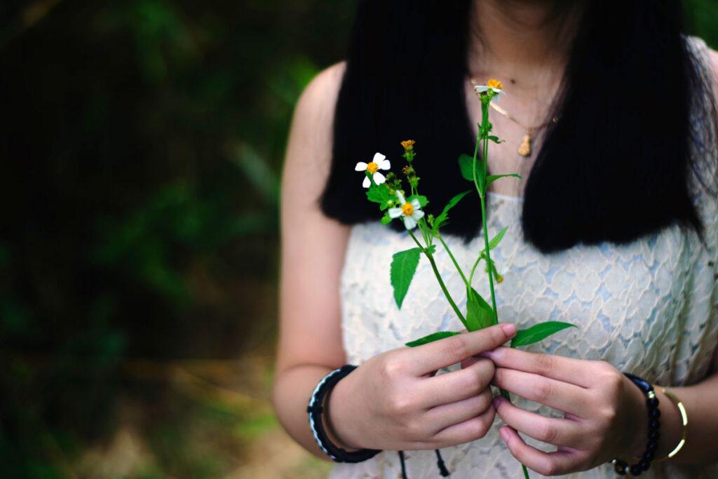 Eine Frau hält ein grüne Pflanze