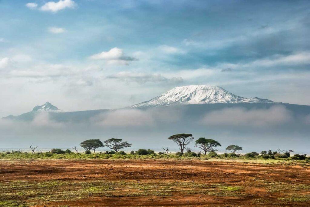 Hinter einem Safari steigen Bergen auf