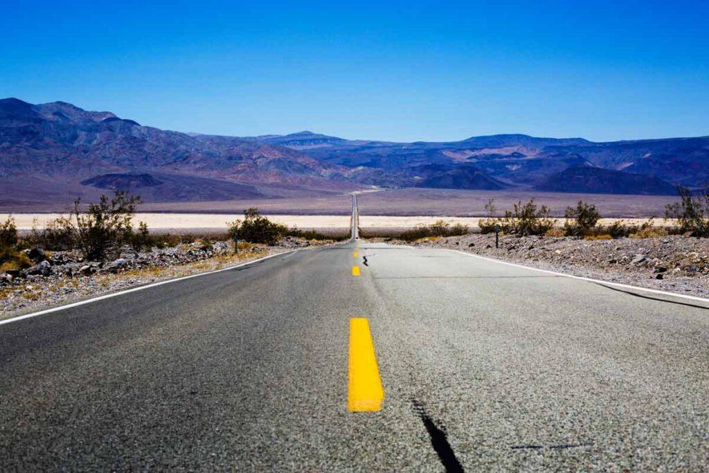 Unter blauem Himmel erstreckt sich eine Straße über den Horizont.