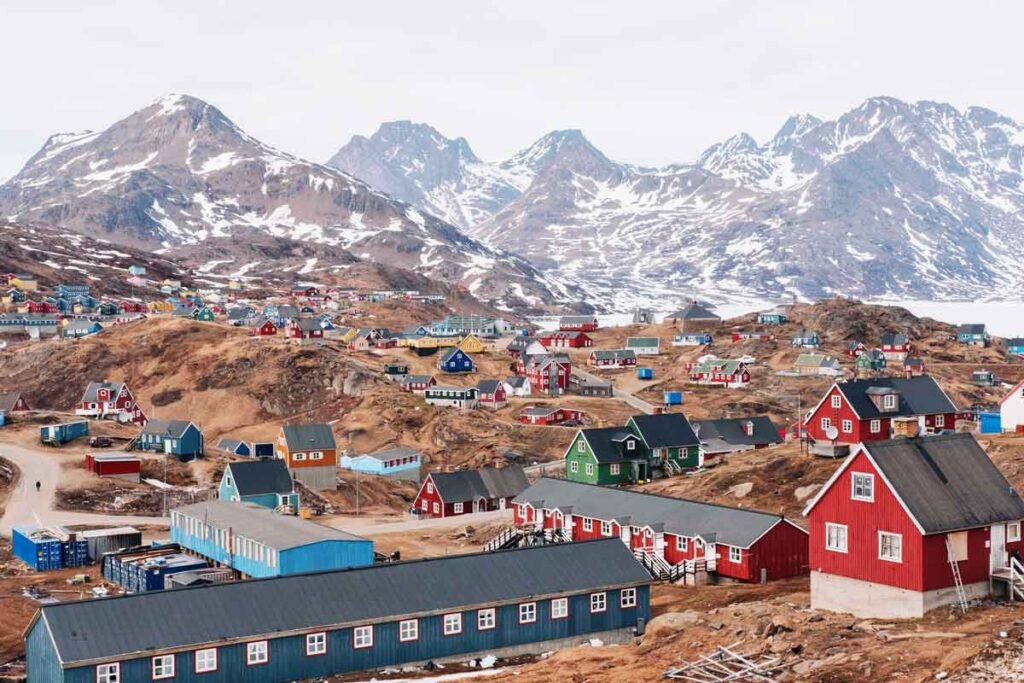 A colourful town lies at the foot of snow-topped mountains