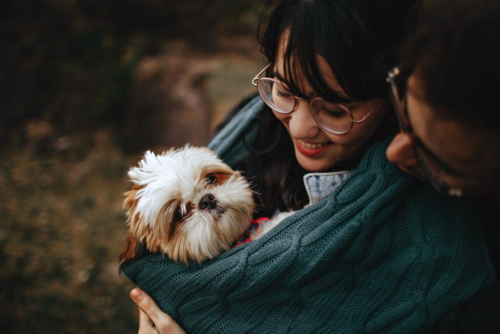 A couple cradle their small dog in a green blanket