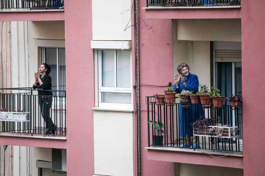 In 2 Balkons applaudieren 2 Frauen