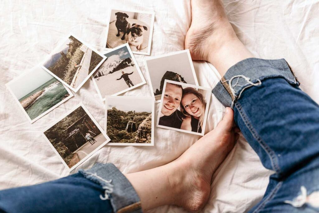 Photos on the bed between someone's legs