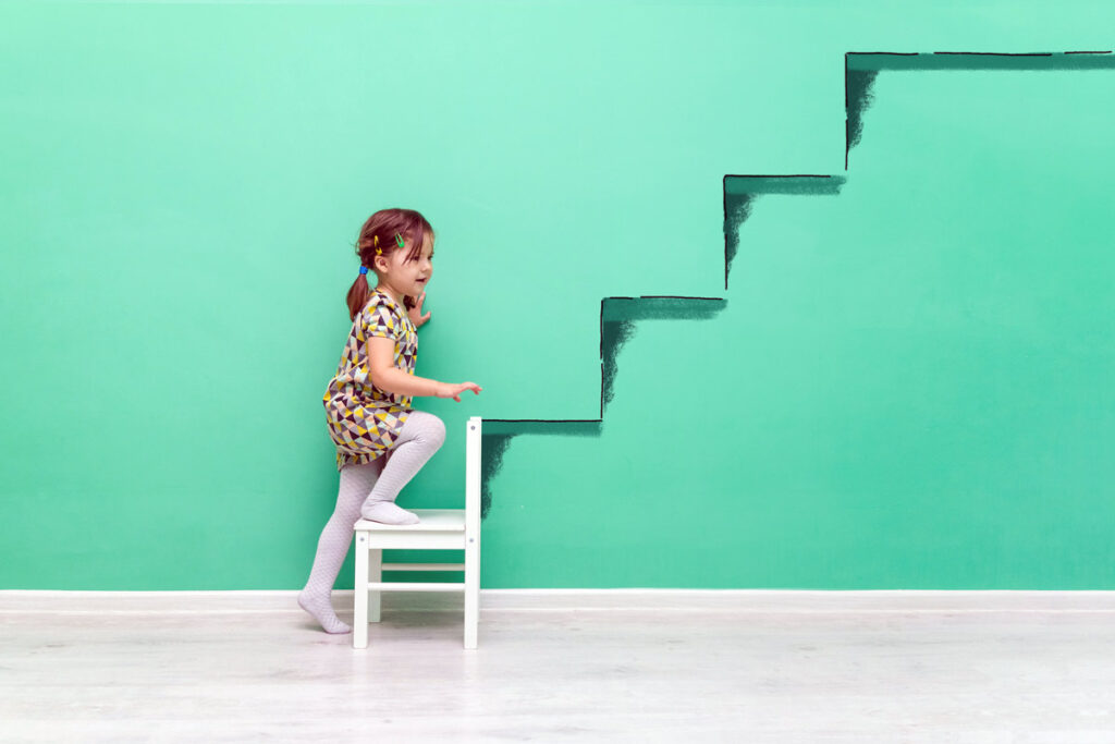 A little girl pretends to climb stairs painted on green wall