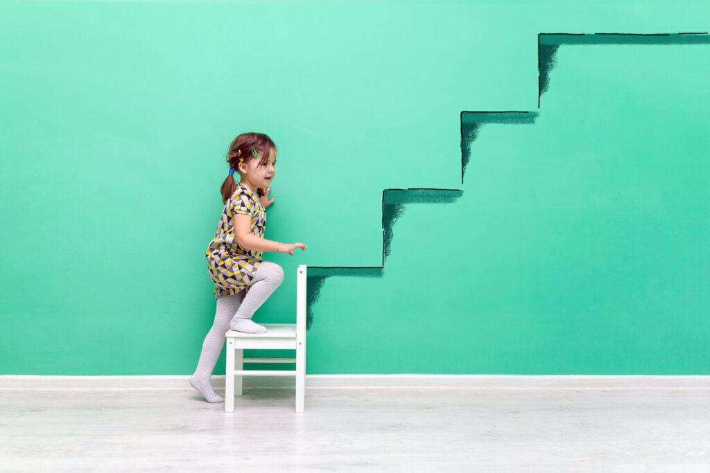 Ein kleines Mädchen klettert an der Wand gemalten Treppen