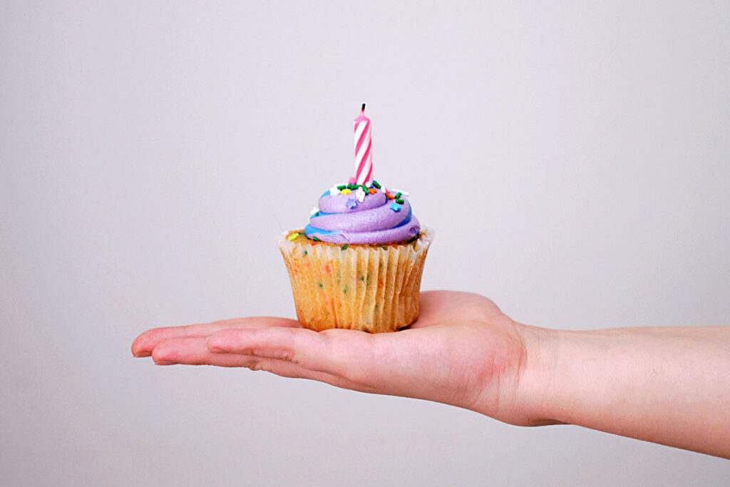 hand holds a cupcake with a candle on top