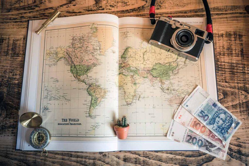 Eine Weltkarte mit Kamera und Geld - starte dein Urlaub zu Hause