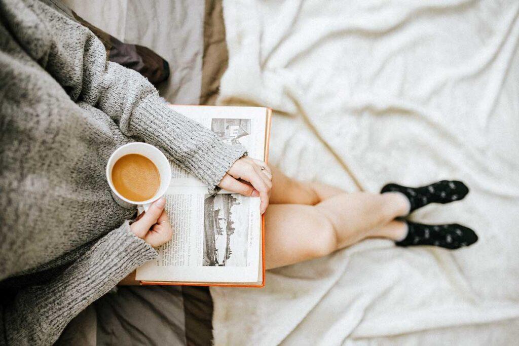 Jemand sitzt mit Kaffee und ein Buch