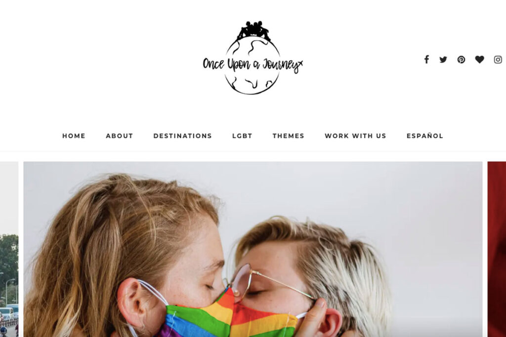 Two women kiss through rainbow masks on Once Upon A Journey homepage