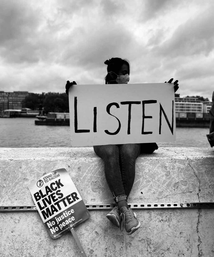 A woman protests for BLM saying 'listen' and showing how to be anti-racist