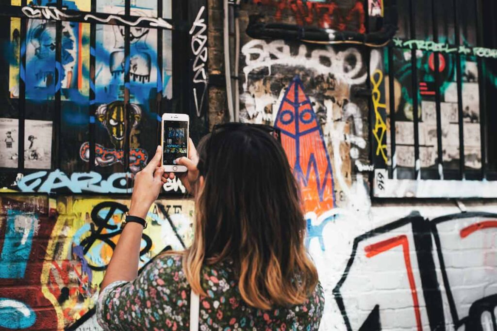 A woman photographs a graffiti wall