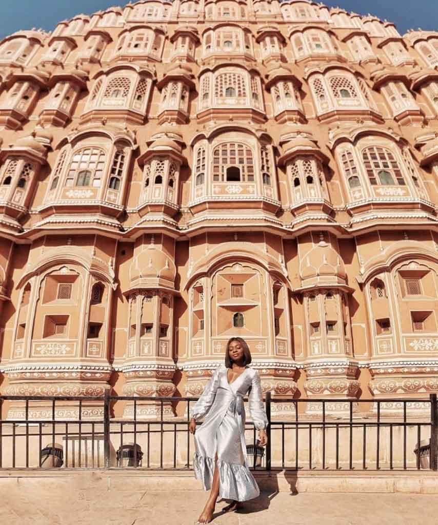 Vor eine riesige Gebäude steht eine Frau im silberen Kleid
