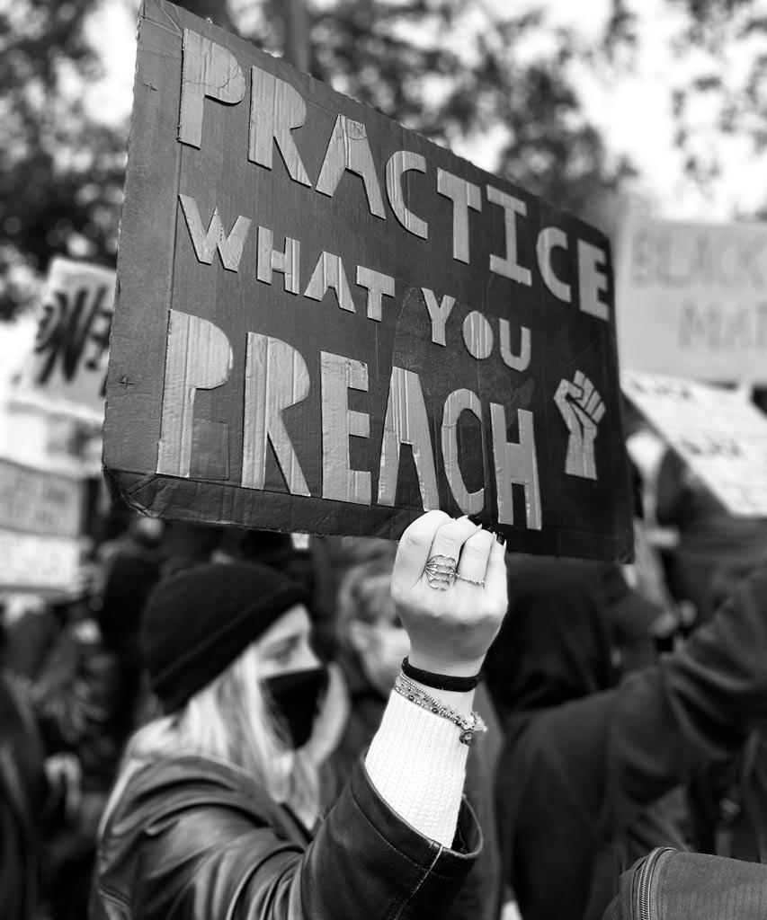 Auf ein BLM Plakat steht 'Tue, was du predigst'