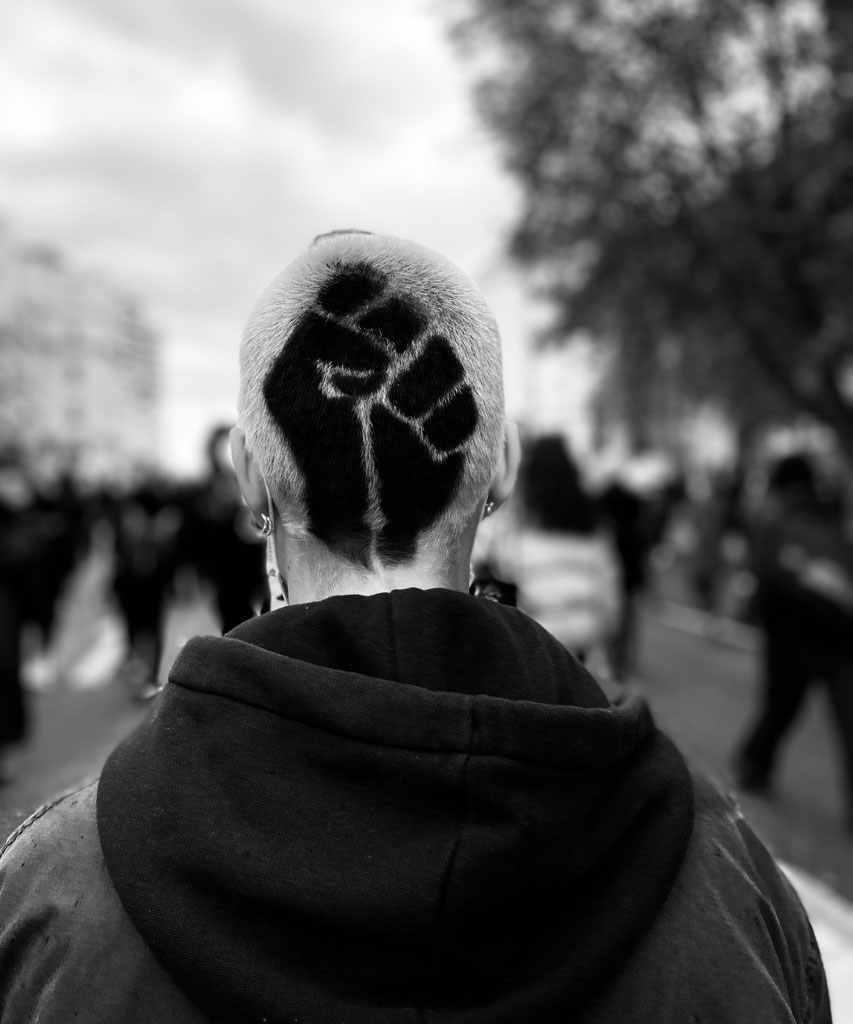 Ein Mann trägt die Black-Power Faust in die Haare
