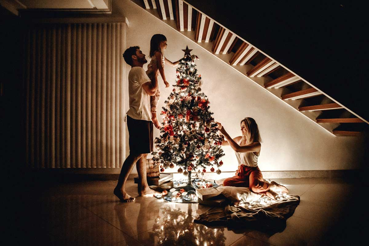 Family decorate a Christmas tree together