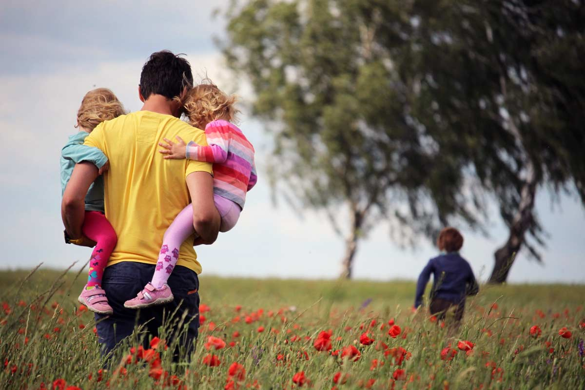 Dad hold two kids in a field