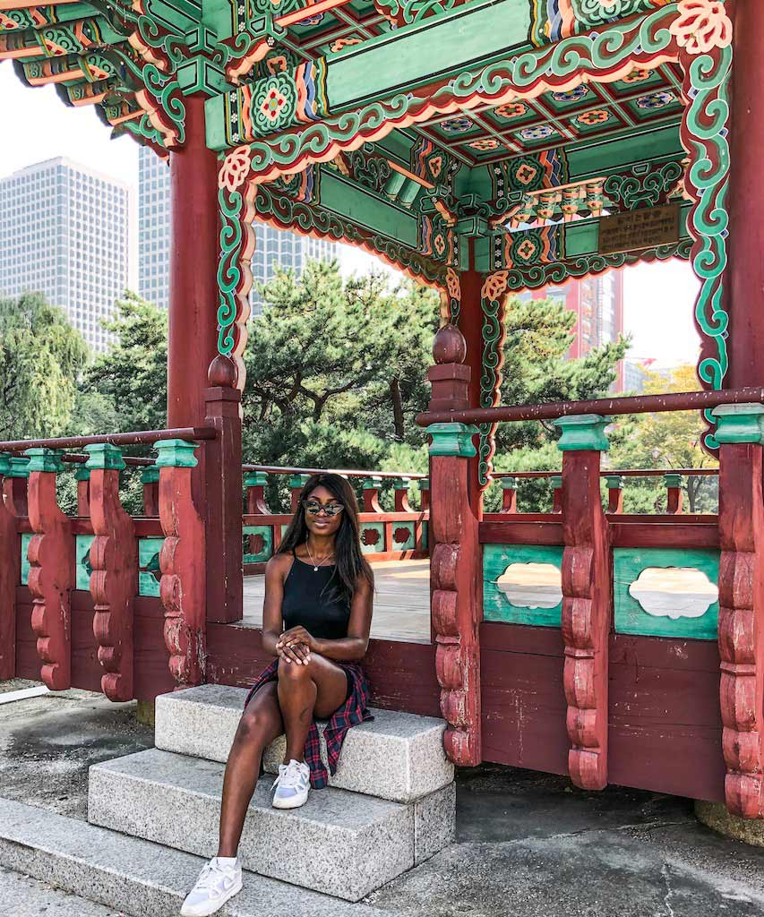 Efia sits on the steps in a beautiful travel destination