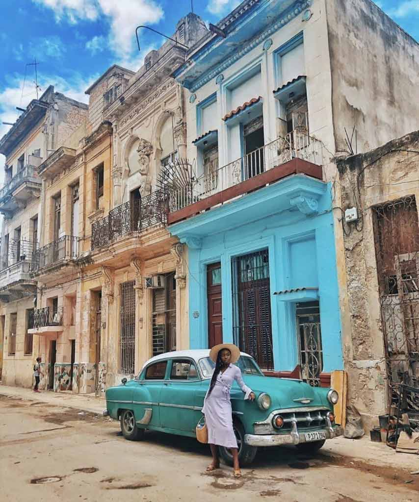 Jessica is in front of a colorful set of buildings as she travels while black