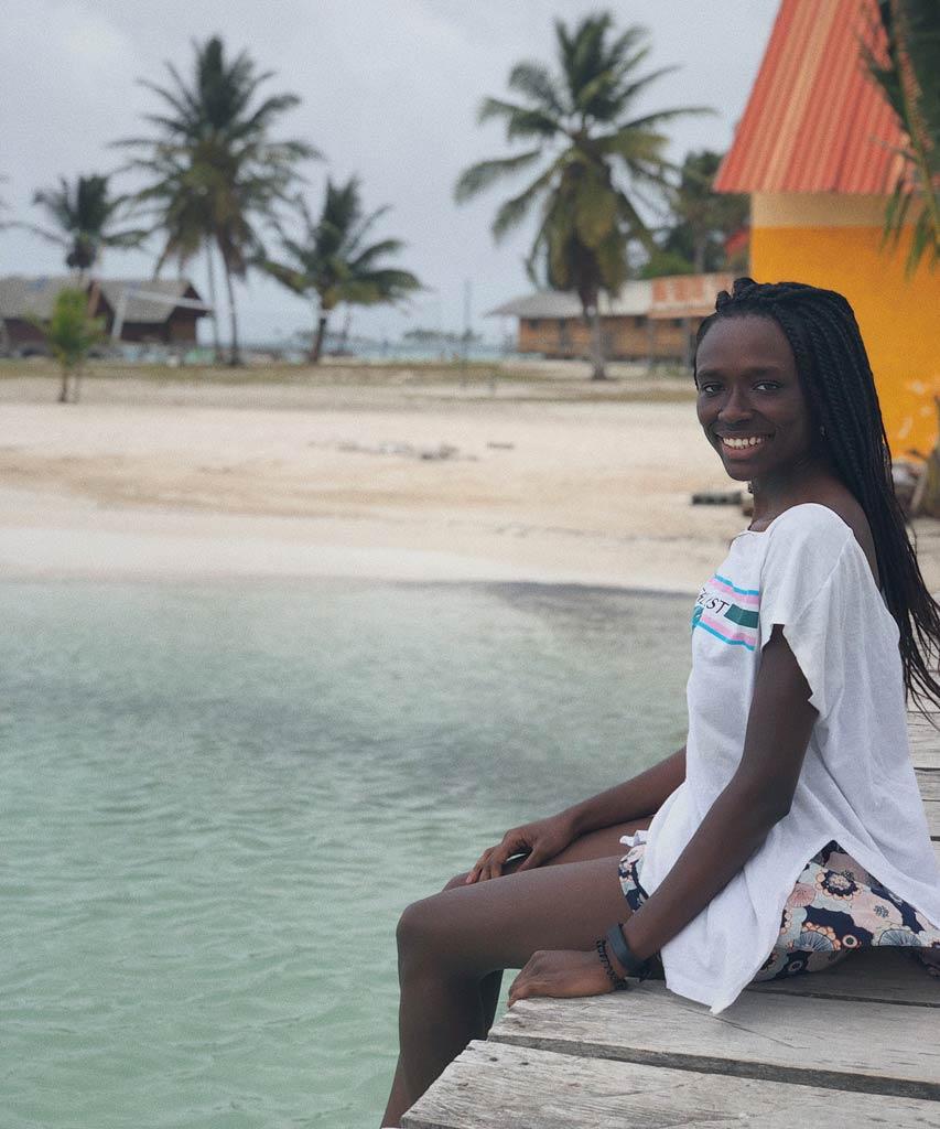 Eine schwarze Frau sitz vor dem Meer