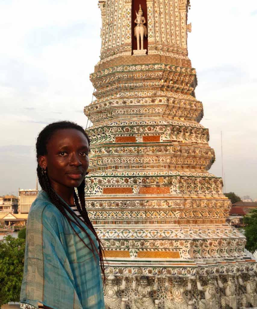 Vor einen großen Turm steht eine Frau