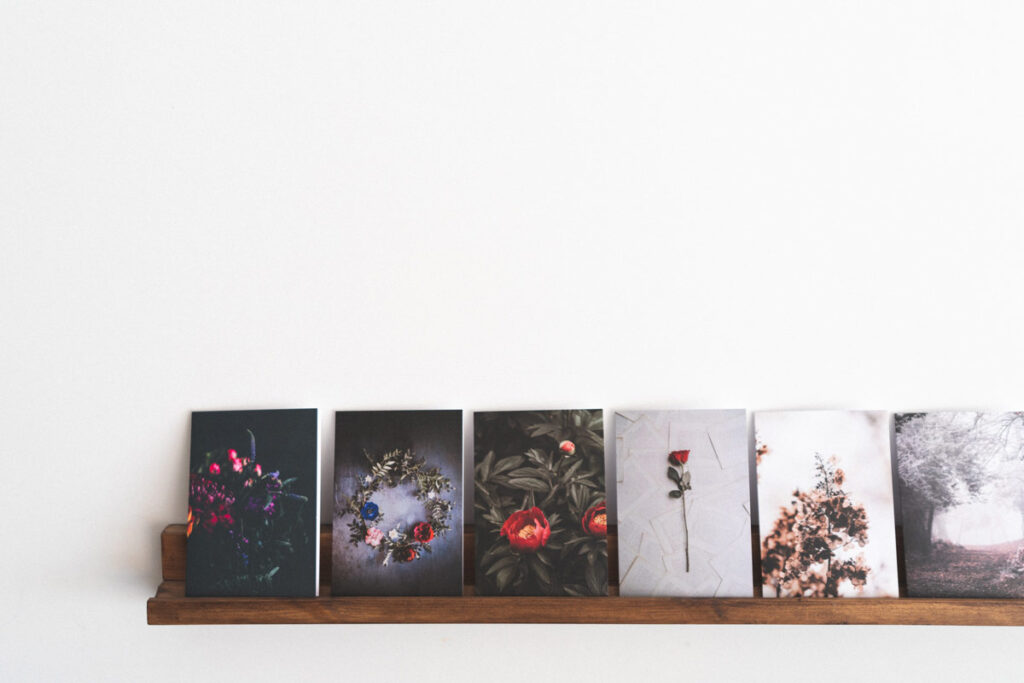 a row of postcards are displayed on a mantlepiece timelessly
