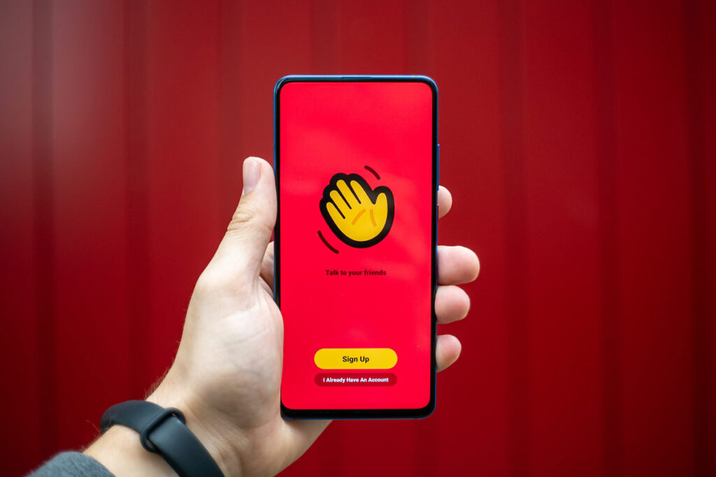 A hand holds a phone with the House Party app for staying connected