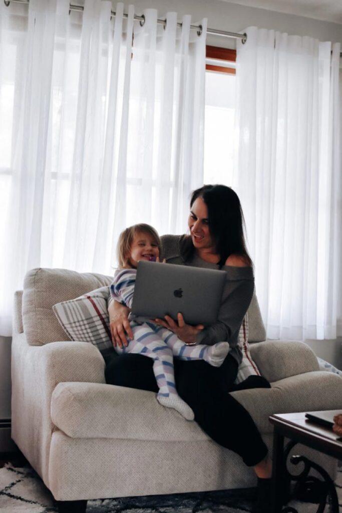 Mutter und Tochter lachen vor einen Computer