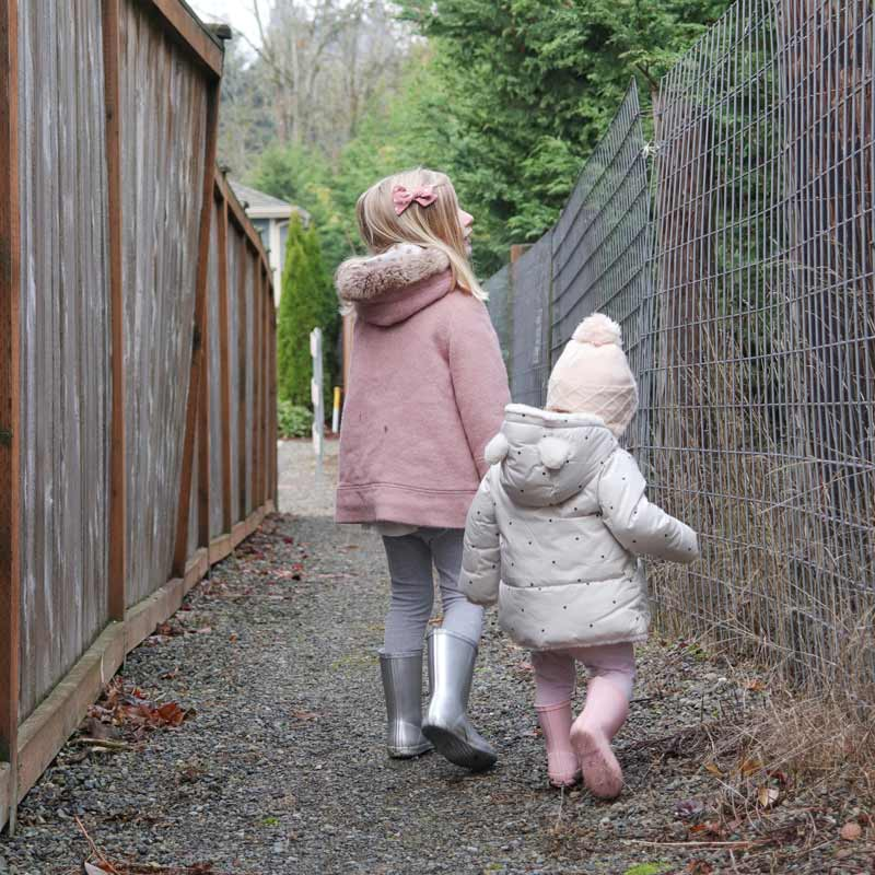 Two little girls search for DIY materials on a walk