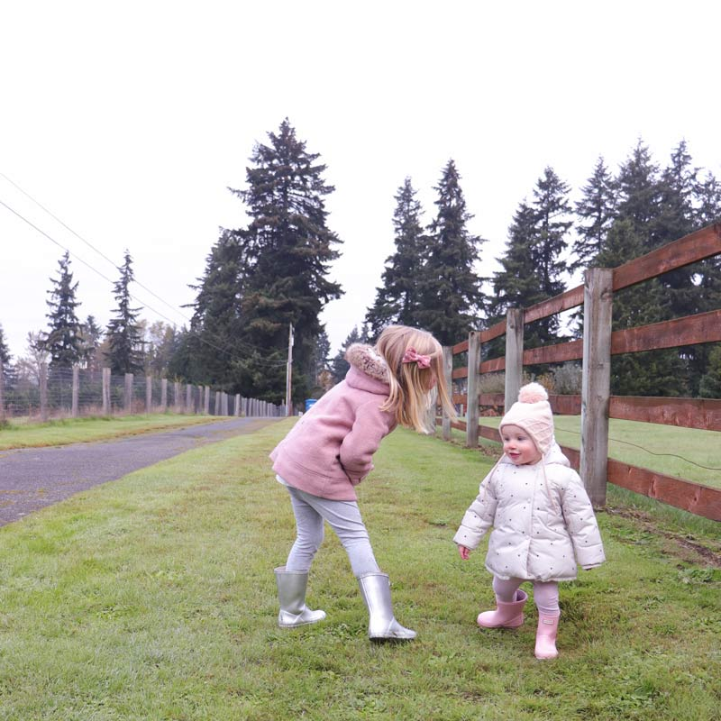 Two kids play on a family walk