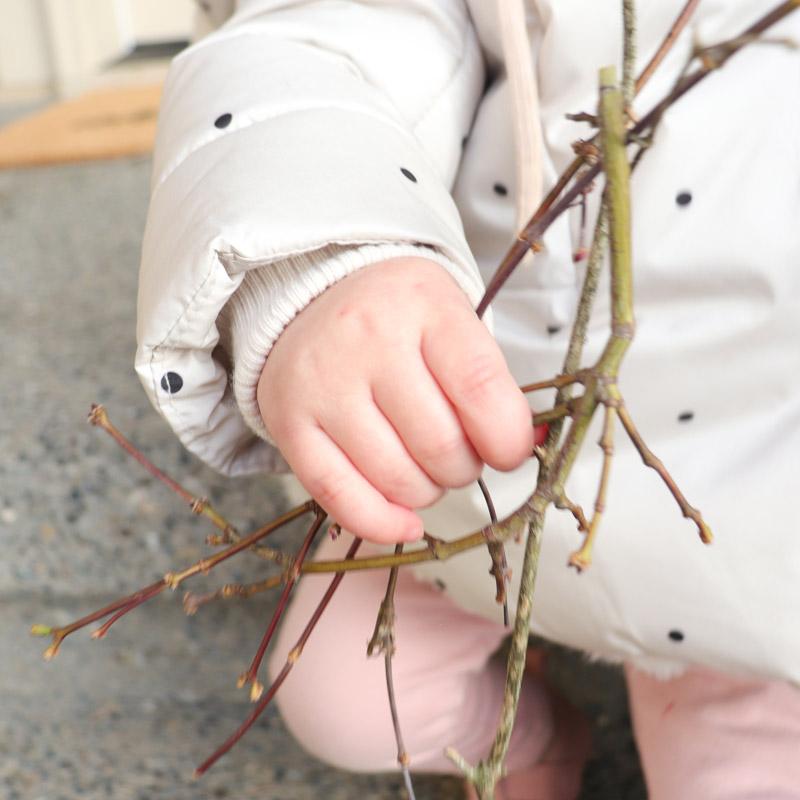 Ein Baby haltet Zweige für das gebastelte Rentier