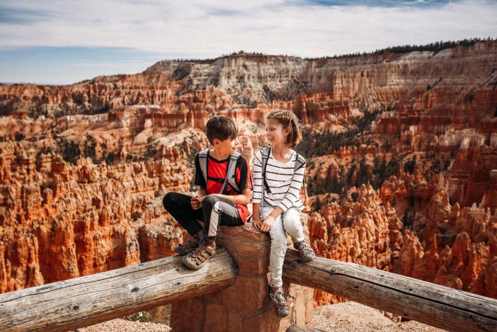 Zwei Kinder sitzen vor den Grand Canyon in der USA