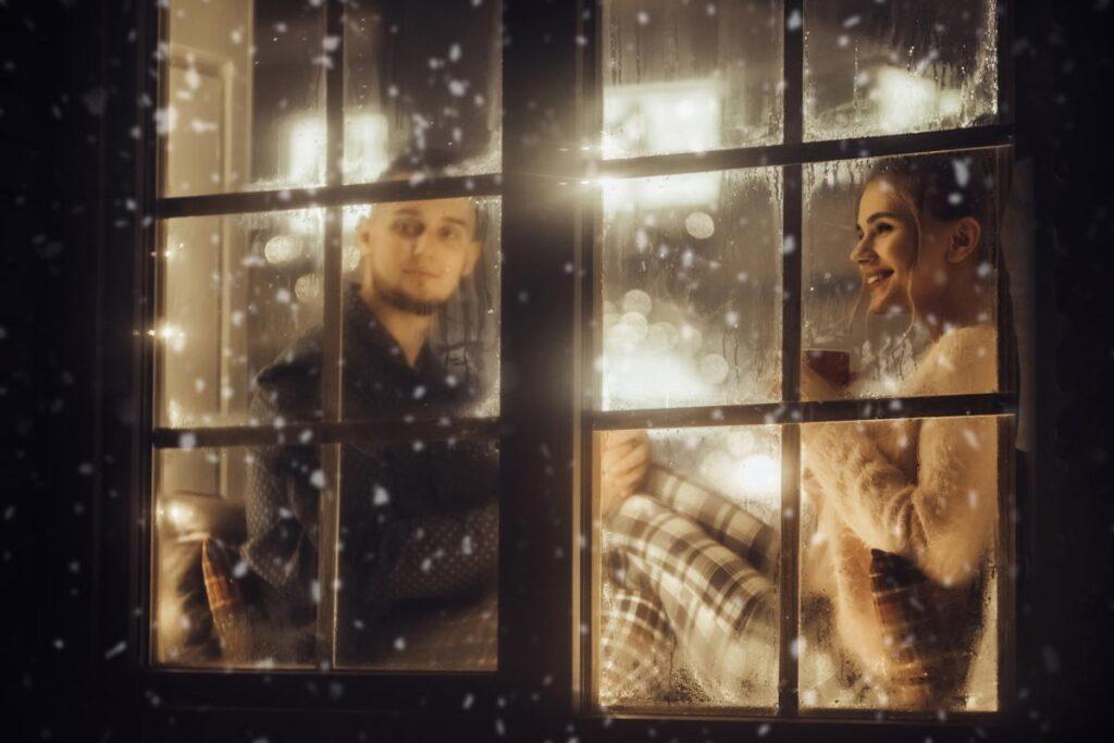 A couple sit in pyjamas in the window