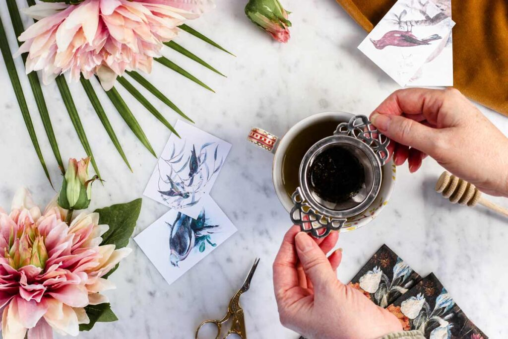 A person holds coffee in this one of our flat lay ideas surrounded by flowers and paintings