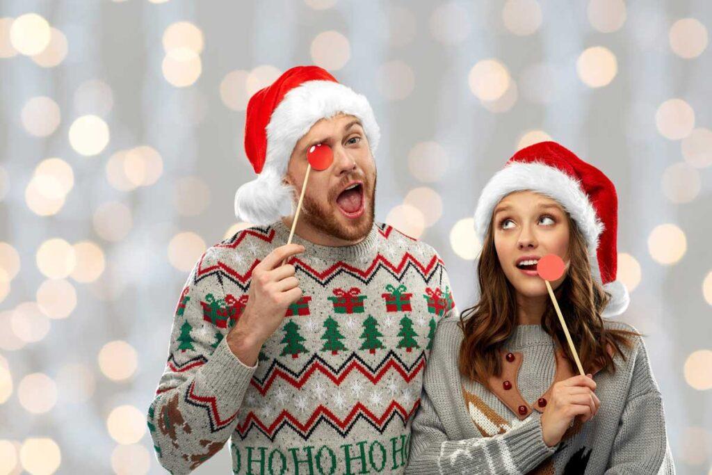 Ein Paar tragen hässliche Weihnachtspullis und Weihnachtsmütze für ein Weihnachtsfoto